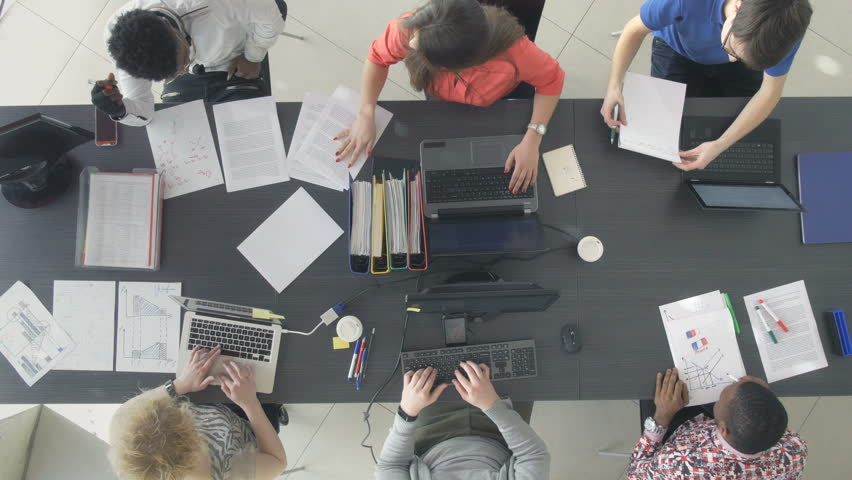 Timelapse of young office workers managing the new online business. View from above of ambitious entrepreneurs sitting at the desk in shared office space. #1007841076