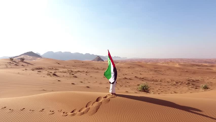 arab emirati man holding UAE flag and walk in the Dubai Desert