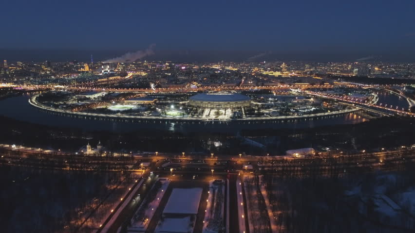 Luzhniki Stadium and Illuminated Moscow Skyline at Frosty Winter Evening. Russia. Aerial View. Drone is Flying Forward and Upward. Establishing Shot.