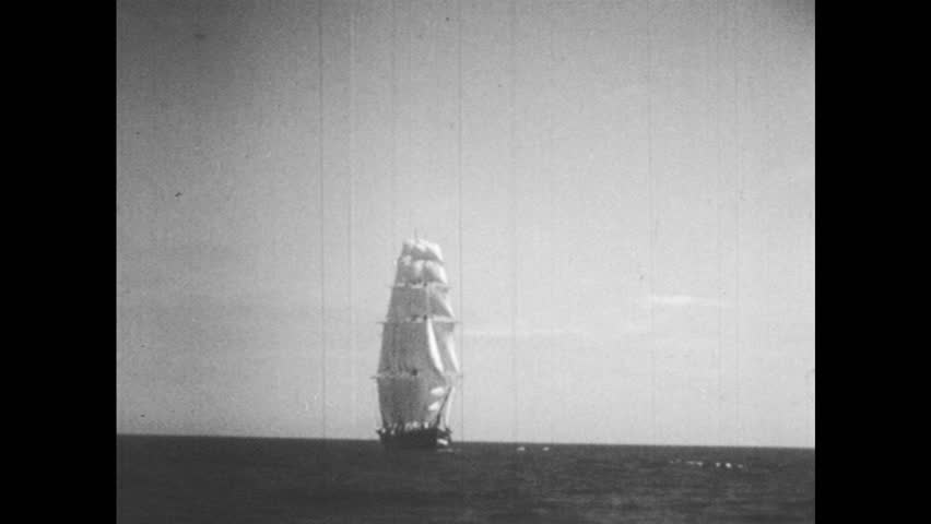 1950s: 19th century sailing ship at sea. 13-star American flag (Betsy Ross Flag) blowing in the wind.