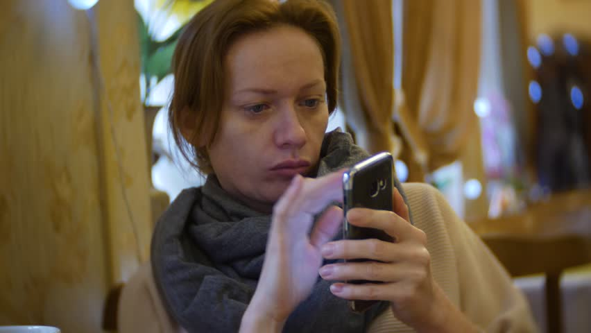 a woman is having dinner in a cafe using a smartphone. 4k #1007855251