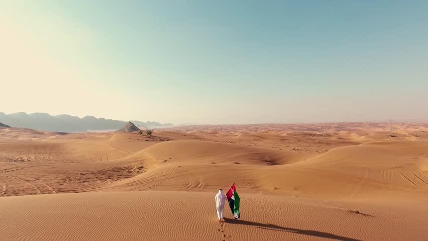 Proud arabian Emirati man holding a UAE flag, walking in the desert  | Shutterstock HD Video #1007860999