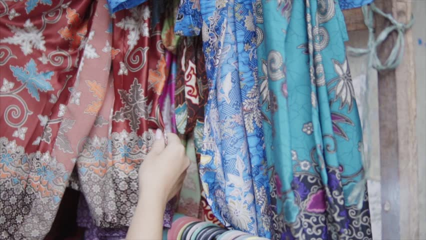 Stand of the colorful embroidered with threads and stamp print clothes in different colours at the traditional etnic asian market. Womans hand trying the quality of the textile material
