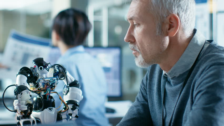 Robotics Engineer Manipulates Voice Controlled Robot, Laptop Screen Shows Speech and Face Recognition Software. In the Background Robotics Reseatch Center Laboratory.