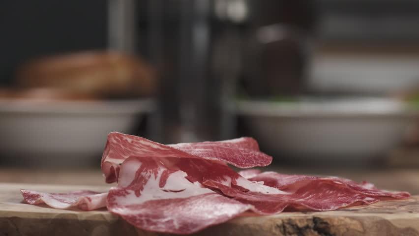 Slow motion of Italian coppa ham falling on wood board closeup | Shutterstock HD Video #1007889718