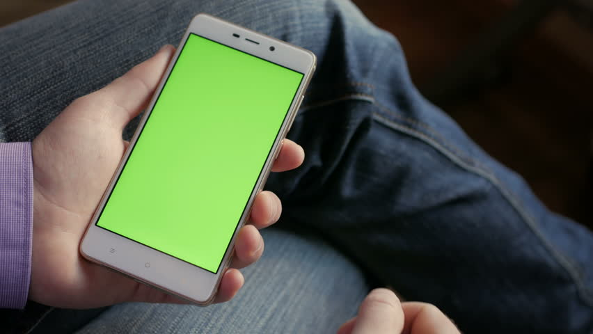Man in the workplace using his smartphone with green screen, scrolling  tapping on screen. Hands top view.  4K Hands holding smart phone CHROME KEY    Shutterstock HD Video #1007890066