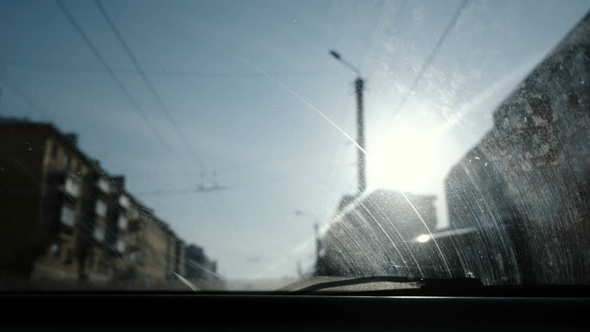 View from the car to the city. Focus on the dirty windshield. #1007893156