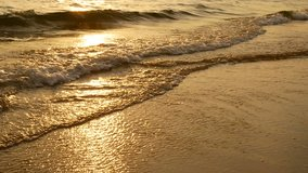 4K amazing sunset over the tropical beach. ocean beach waves on beach at sunset time , sunlight reflect on water surface. beautiful evening nature sea background.