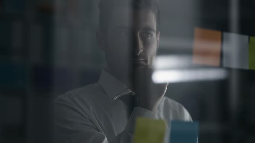 Creative smart businessman examining sticky notes in the office and thinking about innovative business strategies