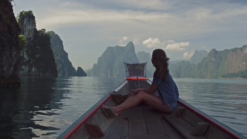 Lifestyle video of pretty travel woman sitting in wood long tail boat on tropical limestone cliffs . Explore and vacation concept. Khao Sok lake, Thailand. #1007907979