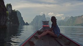 Lifestyle video of pretty travel woman sitting in wood long tail boat on tropical limestone cliffs . Explore and vacation concept. Khao Sok lake, Thailand.