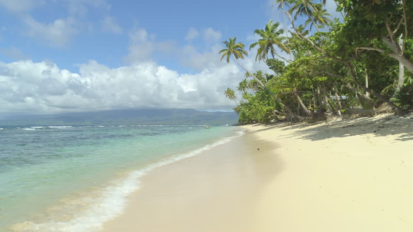 LOW ANGLE VIEW: Beautiful sunlit sandy beaches on Fiji island perfect for unwinding. Local wooden boat anchored near the shoreline surrounded with surfers. Popular tourist spot for surfing enthusiasts | Shutterstock HD Video #1007925940