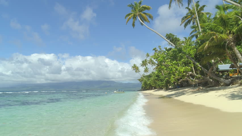 LOW ANGLE VIEW: Beautiful sunlit sandy beaches of Fiji island perfect for unwinding. Local wooden boat anchored near the shoreline surrounded with surfers. Popular tourist spot for surfing enthusiasts | Shutterstock HD Video #1007925976