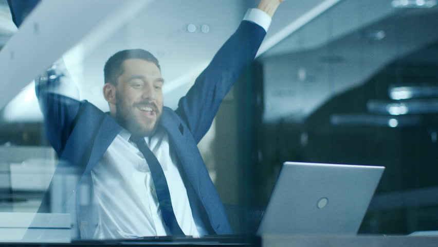 In the Office Businessman Sitting at the Desk Using Laptop Finishes Project and Wins Big. Makes Successful Gestures Raises Arms in Celebration. Shot on RED EPIC-W 8K Helium Cinema Camera.