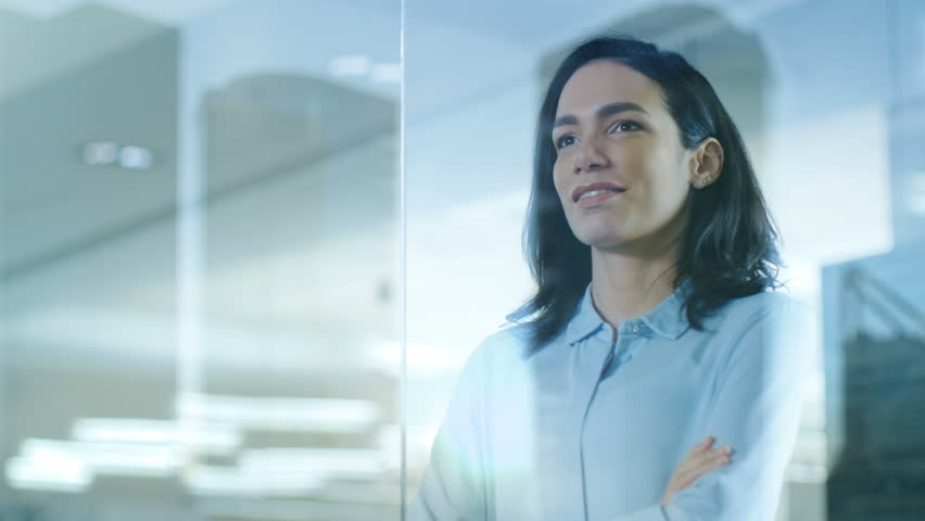 Beautiful Female CEO in Her Office Looks out of the Window on a Big City. Strong Independent Woman with Big Accomplishments Behind and Ahead of Her. Shot on RED EPIC-W 8K Helium Cinema Camera.