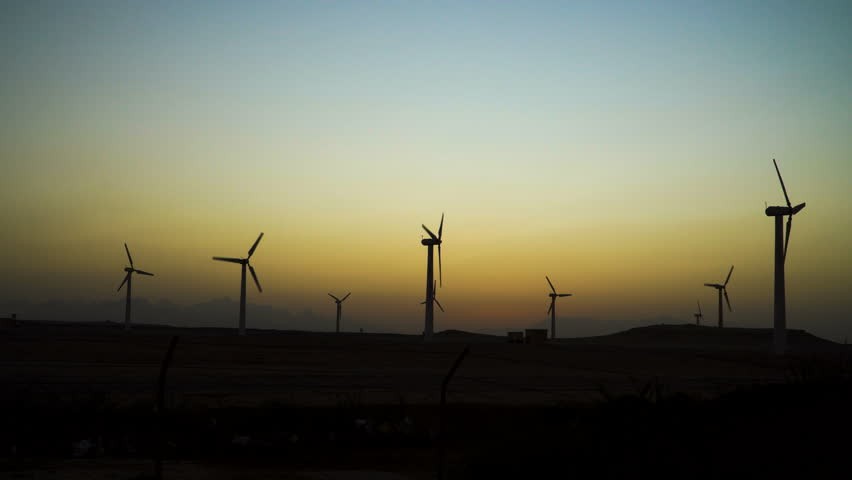 4K Beautiful windmill turbines harnessing clean, green, wind energy silhouetted in the sunset sky with sun rays. Green energy. | Shutterstock HD Video #1007932924