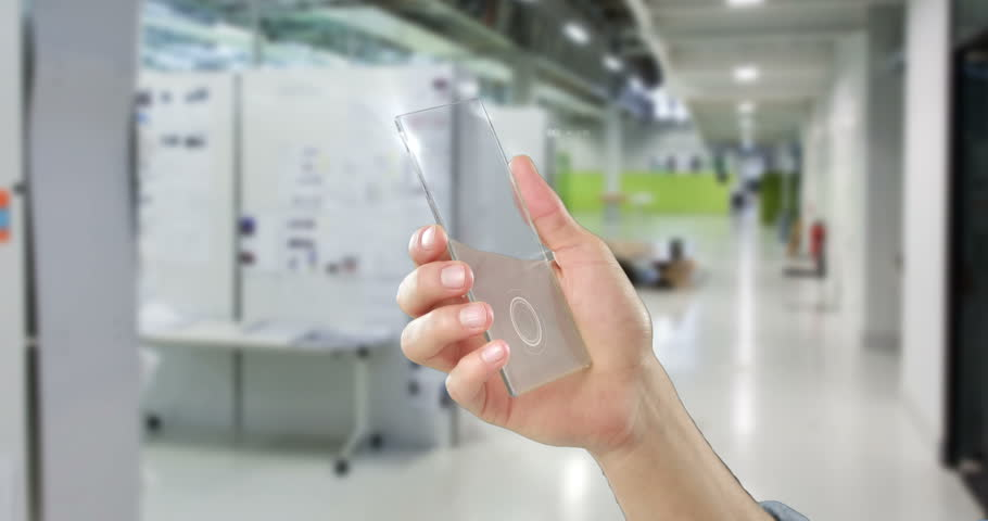 Close-up of hand holding futuristic mobile phone in office | Shutterstock HD Video #1007936320
