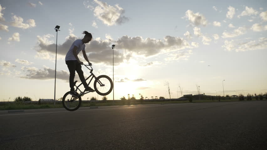 Slow motion of hipster young man losing control of bike failing jump trick