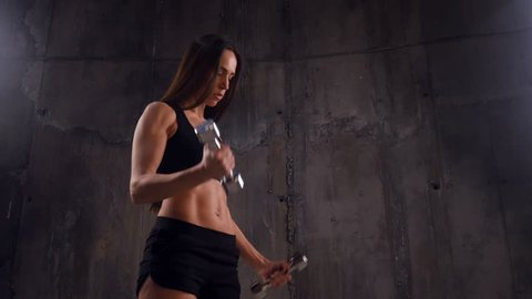 Good-looking woman performing sport exercise with double dumbbells
