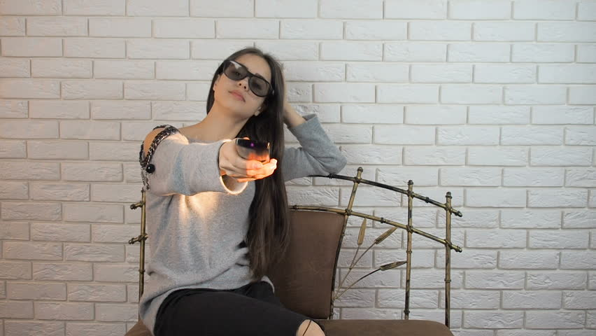 Beautiful girl in front of the TV. Girl in 3D glasses with remote control from the TV | Shutterstock HD Video #1007950549