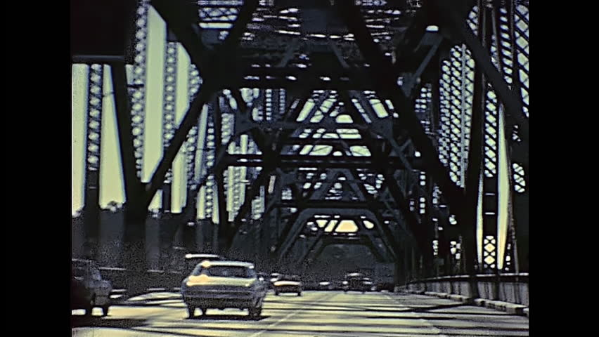 POV of vintage car crossing Oakland Bay Bridge passing by Treasure Island to Oakland. Archival footage in eighties. San Francisco, California, United States in 1980. | Shutterstock HD Video #1007977906