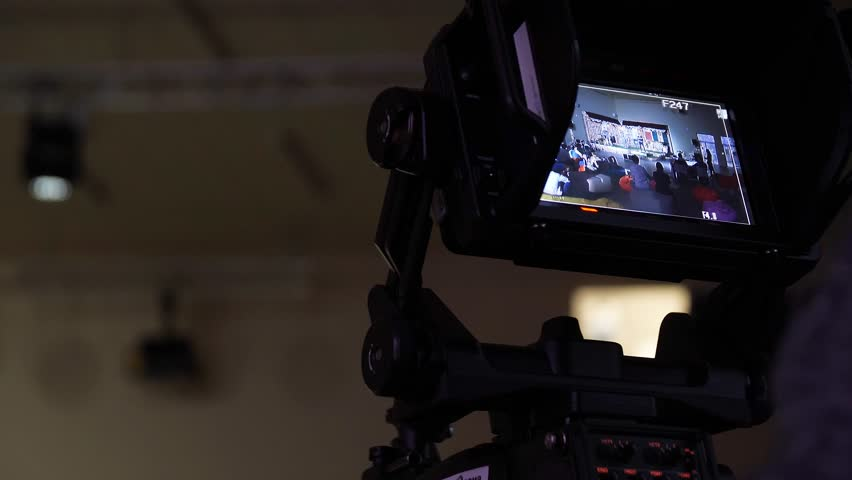 Behind the scene of tv movie video film shooting production crew team and camera lighting set in the big studio. Professional digital video camera in studio. Cameraman working with announcer in
