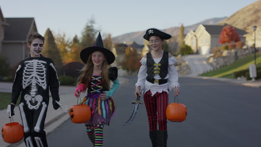 Front view tracking shot of children walking in neighborhood on Halloween / Cedar Hills, Utah, United States