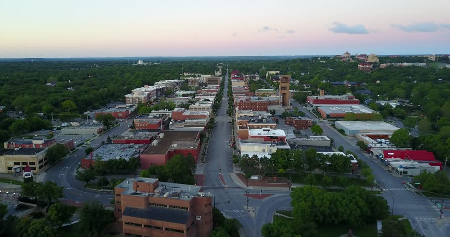 An aerial drone flight over the downtown area of a small town during sunrise. Flight is in Lawrence, Kansas along Massachusetts Street.