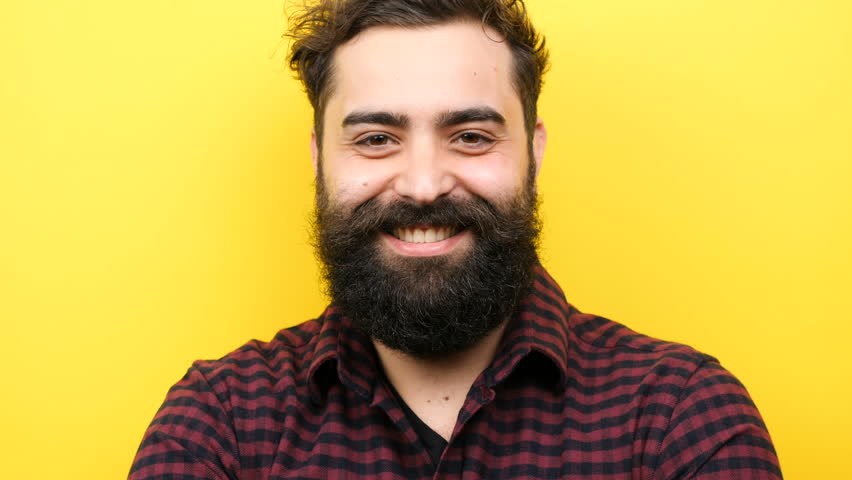 Happy smiling long bearded hipster winking silly on yellow background | Shutterstock HD Video #1007993161