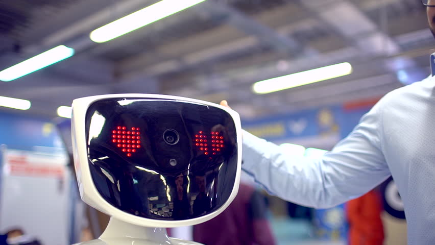 Visitors man talking with humanoid robot. slow-motion. A robot with a display shows emotions, talking, confesses in love. Robot fell in love heart emotions. artificial intelligence, virtual love, vr