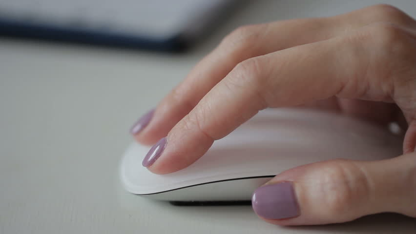 Woman is holding white stylish mouse by her hand, close up. Lady is working on computer and using brand-new device to cooperate with the machine. Female office worker is scrolling the pages by her