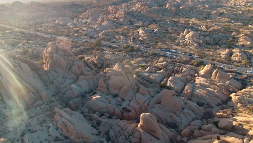 Sun shines brightly as drone circles above Hall of Horrors rock formations in Joshua Tree National Park
