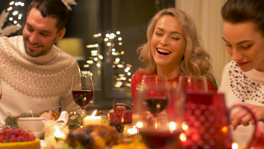 Holidays and celebration concept - happy friends having christmas dinner party at home and eating and drinking wine | Shutterstock HD Video #1008023074