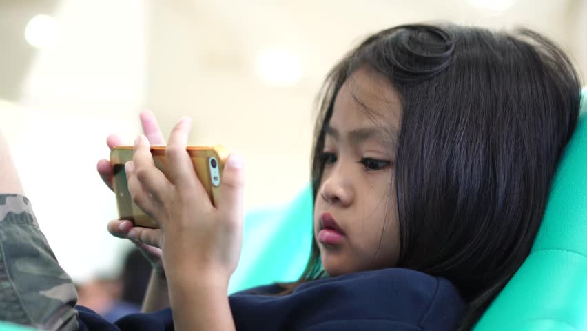 Little girl using mobile phone for looking media and playing games , video for education and family concept | Shutterstock HD Video #1008027844