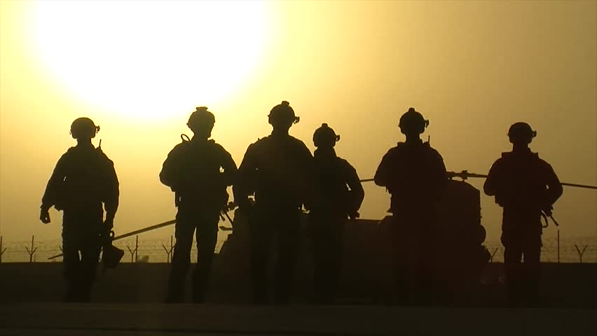 Afghanistan - February 26, 2008: Slow motion of silhouette of soldiers walking at a base in Afghanistan at sunset