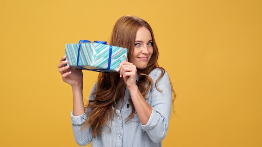 Smiling ginger woman in denim shirt puts on her hat and looking at camera over yellow background