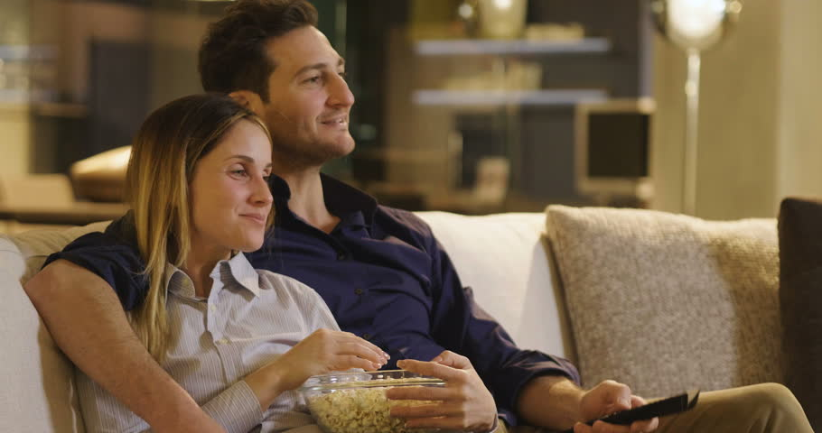 A couple of lovers watch television embraced on the sofa in the new house and watch a movie together. Concept of: leisure, relax, tv.