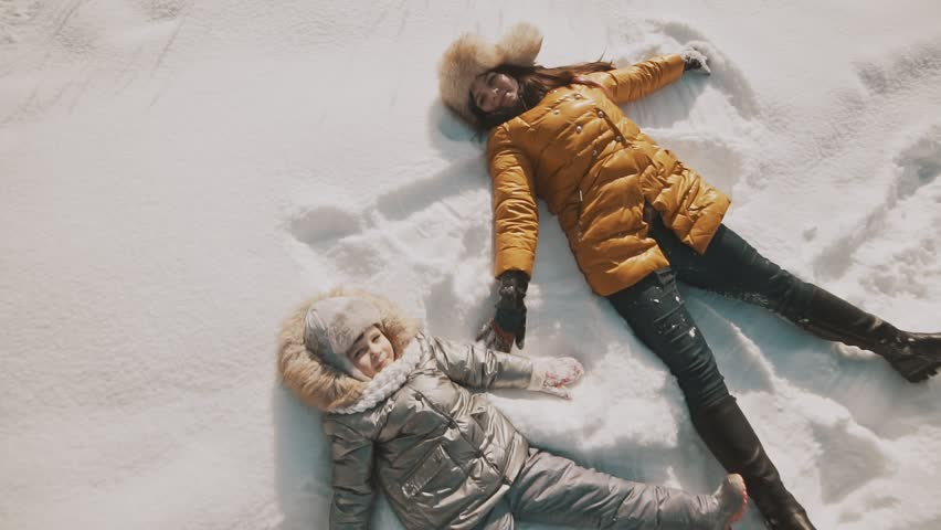 Young mother and little daughter making angels on the snow. Top view with copyspace. Family have fun in sunny winter day outdoors