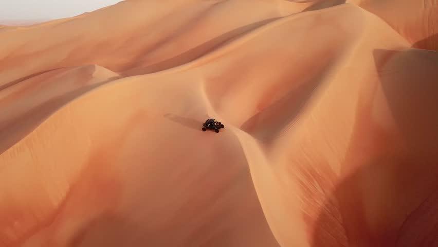 Black dune buggy dune bashing over desert dunes. It's a popular past time for young Emirati men in the Empty Quarter desert. Abu Dhabi, UAE.