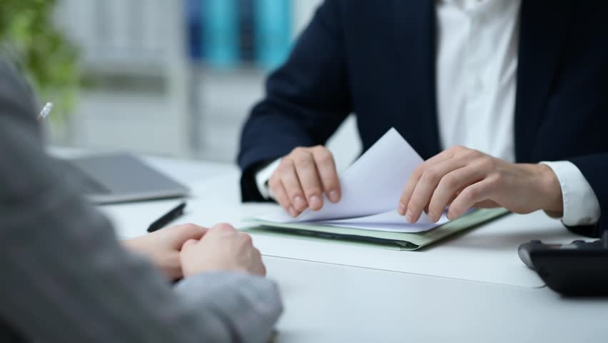 Business people meeting in the office and signing a contract, the man is pointing and giving explanations, agreement and partnership concept Royalty-Free Stock Footage #1008065323