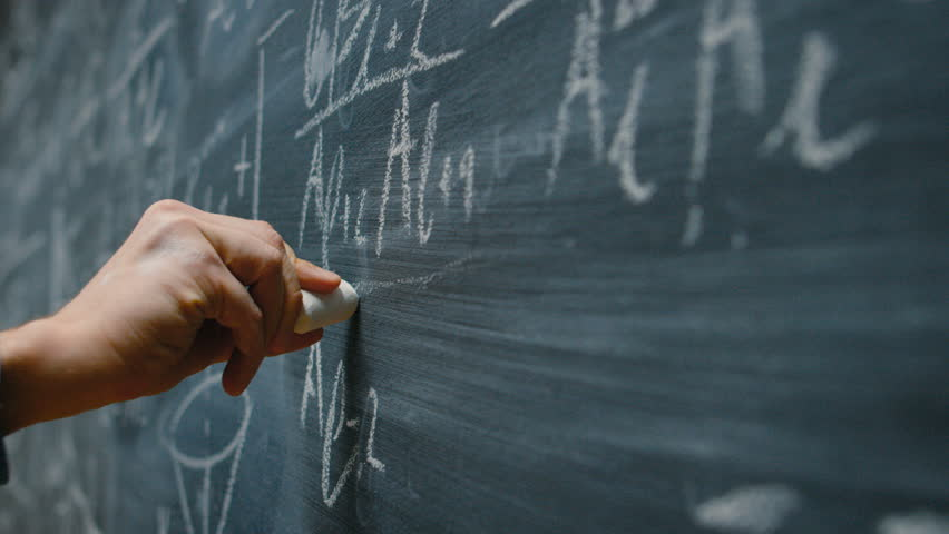 Hand Holding Chalk and Writing Complex and Sophisticated Mathematical Formula/ Equation on the Blackboard. Shot on RED EPIC-W 8K Helium Cinema Camera.