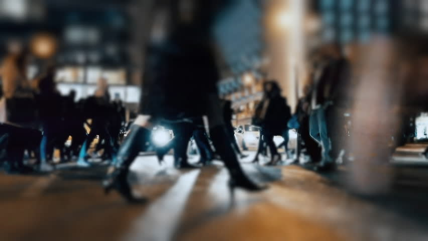 An anonymous crowd of pedestrians walking and crossing a busy city street. No logos, faces visible. Commercial shot. #1008066814