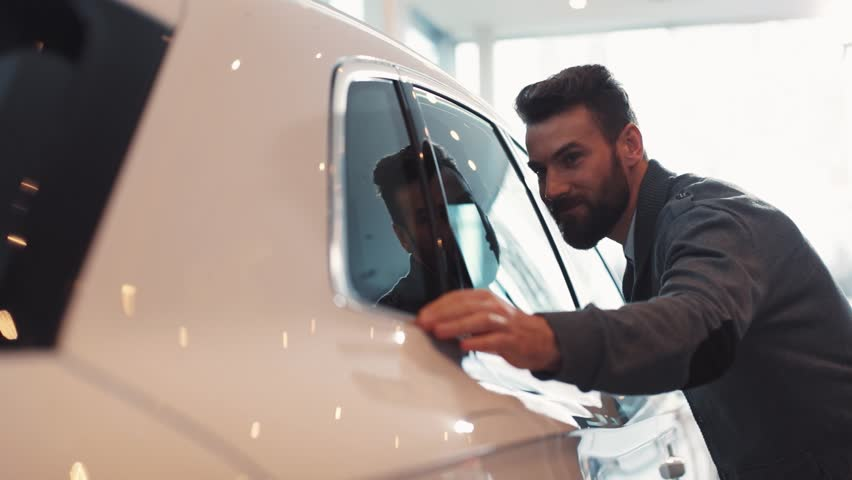 Young man with beard looking carefully at car in car dealership. Guy touching side window of beautiful shiny white car. | Shutterstock HD Video #1008067564