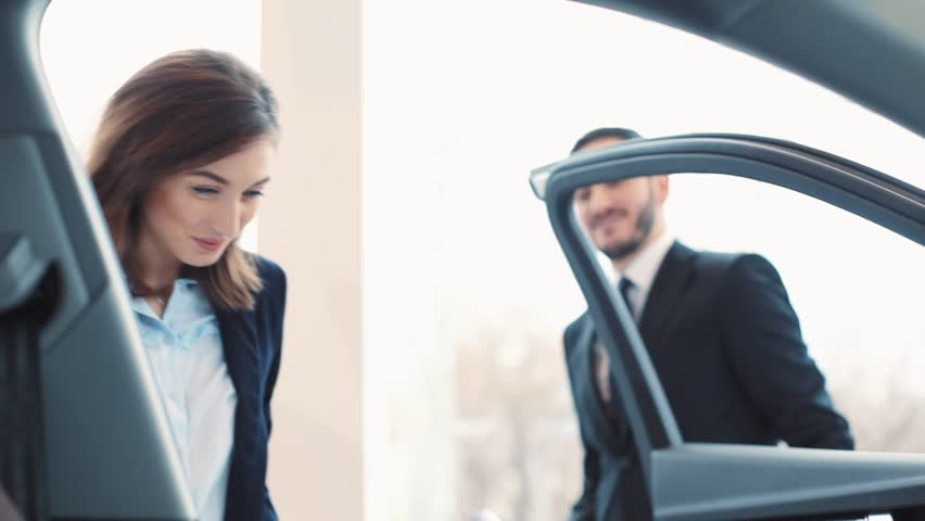 Beautiful young businesswoman buying new car. Consultant giving car keys. Happy girl sitting on driver's seat, holding wheel. Smiling.
