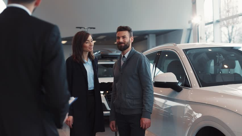 Young couple in love buying new car in car dealership. Happy people hugging. Young attractive man with beard opening door for girl. Young pretty woman sitting.
