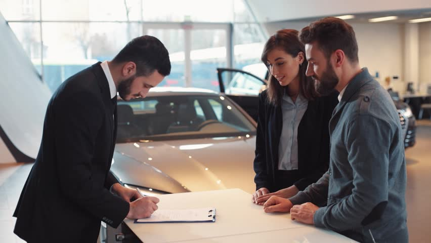 Seller signing contract, giving pen to man. Young guy putting signature on document. Seller giving keys of car on background of beautiful new cars.
