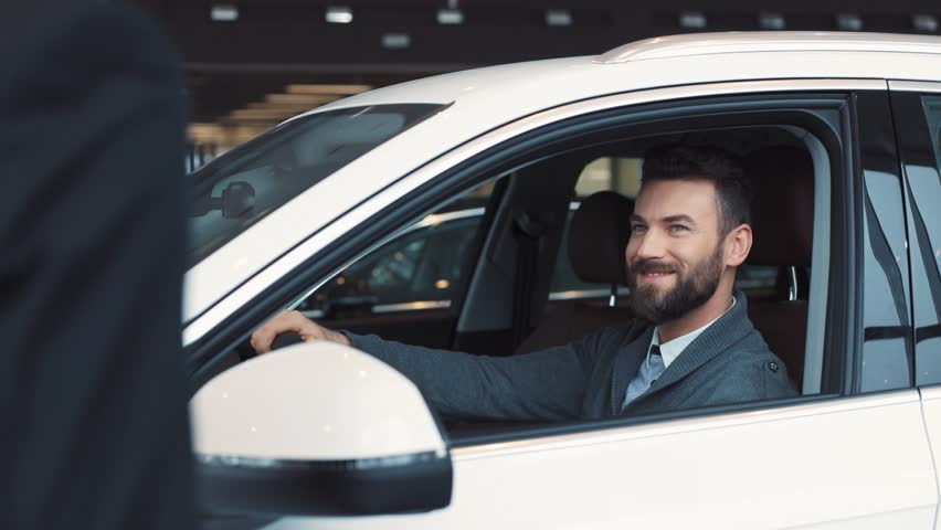 Guy in casual clothes opening car door and sitting on driver's seat. Seller giving keys. Young confident man with beard chewing gum, turning on light in car's interior. | Shutterstock HD Video #1008068083