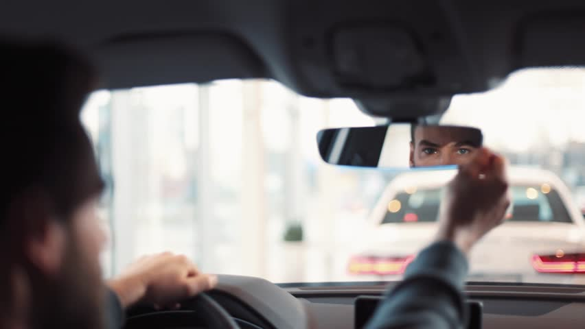 Man sitting at wheel of new car. Young handsome man with beard regulating and looking at rearview mirror. | Shutterstock HD Video #1008068107