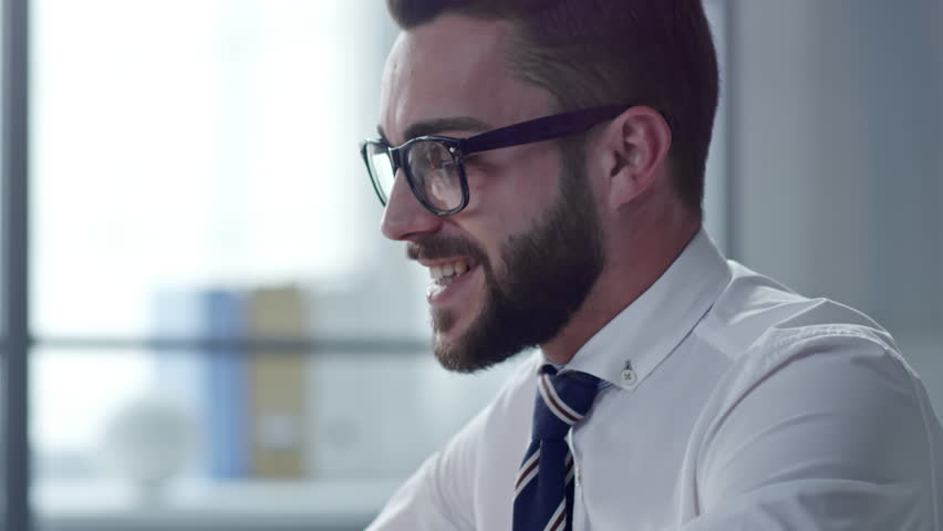 Tilt up of young businessman greeting colleague and talking at web camera of laptop while video conferencing in office   Shutterstock HD Video #1008084769