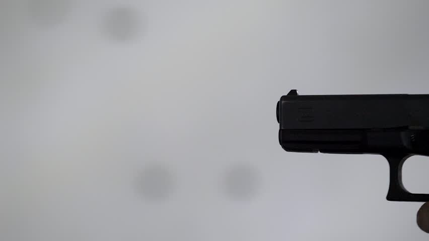 Close profile of man holding a 9 mm handgun, then takes a shot. | Shutterstock HD Video #1008091594